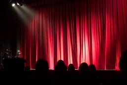 an empty theatre stage with a red curtain viewed from the perspective of the audience