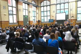 a large conference room full of people watching Maria Balshaw deliver a talk