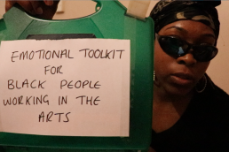 a woman wearing sunglasses and a head scarf holds a first aid kit up to the camera, a sticker on the kit reads: Emotional Toolkit for Black People working in the Arts