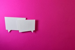 to pieces of cardboard cut into the shape of speech bubbles against a pink backdrop, representing conversation